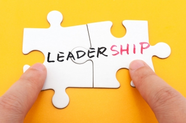 Hand holding two matching white paper jigsaw puzzles which written leadership word